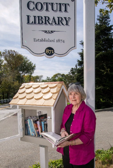 Library volunteer Sally Schumann with the new book kiosk at the Cotuit Library. Photo by Alan Belanich