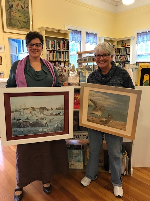 Antonia Stephens, Library Director and Lori Scudder, Friends President display the two smaller pieces of artwork as they stand in the Children's section.
