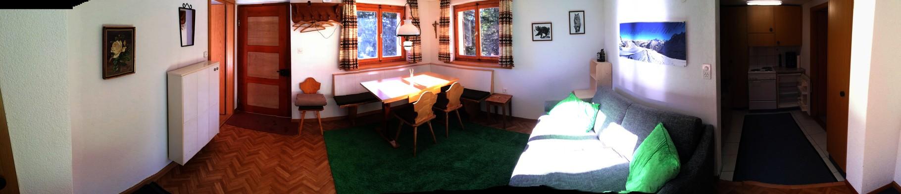 Blick ins Wohnzimmer mit Esstisch und Bettsofa