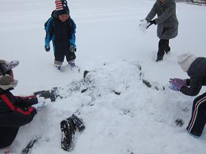 雪にダイブした隊長に隊員が雪をかぶせていきました