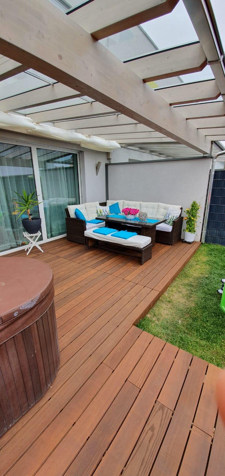 Terrassenüberdachung mit Glaseindeckung und Terrasse mit Thermo-Esche Dielen gebürstet