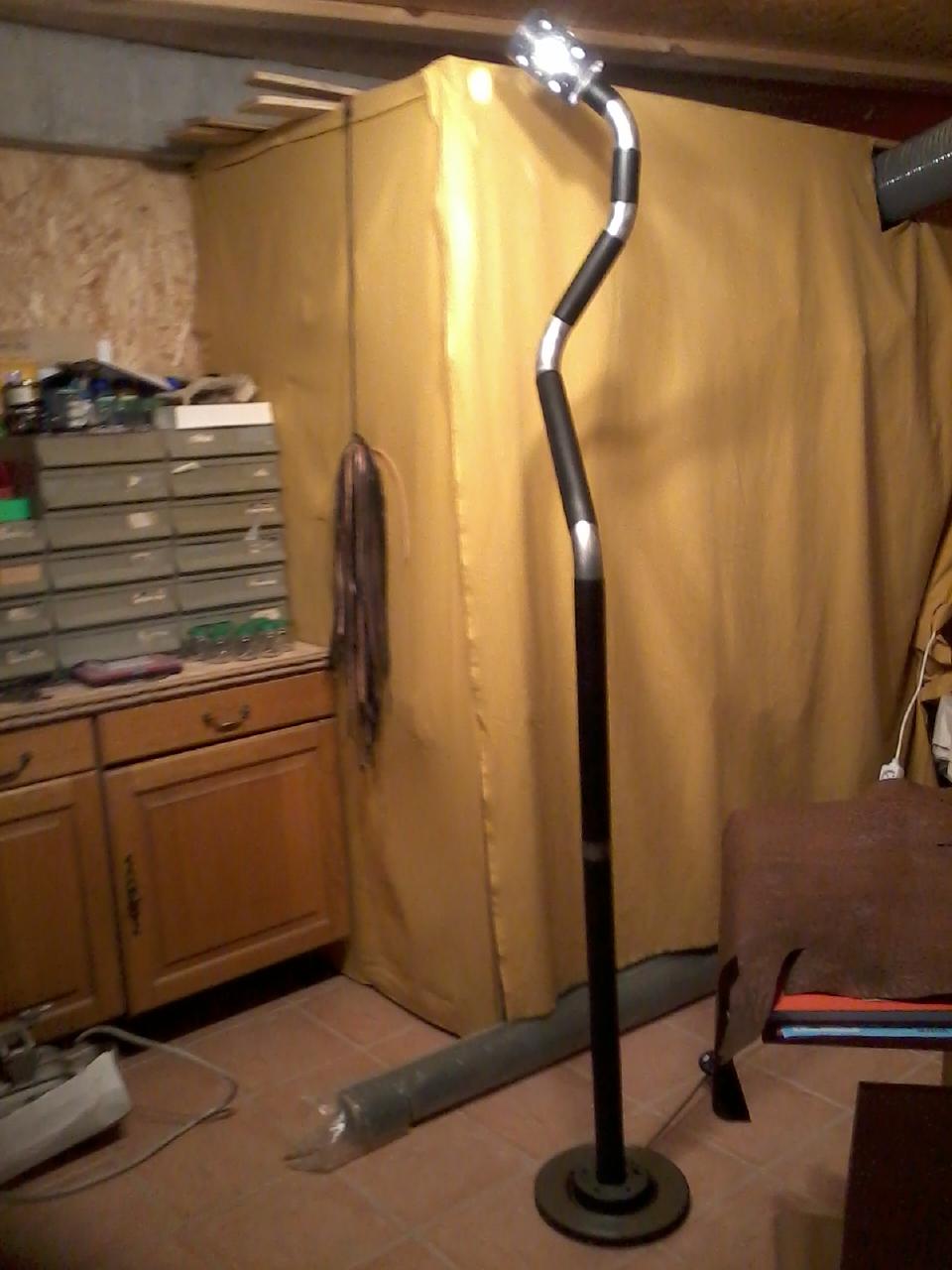 lampe d'apoint  sur un pied en pot d'échappement gainé de cuir noir avec abat jour en cuir vachette tannage végétal teinté