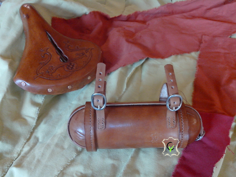 saccoche de selle de vélo, forme tubulaire avec deux demi coquille de chaque cotés, en deuxième plan, la selle finie avec un motif personnalisé en repoussage et une teinture