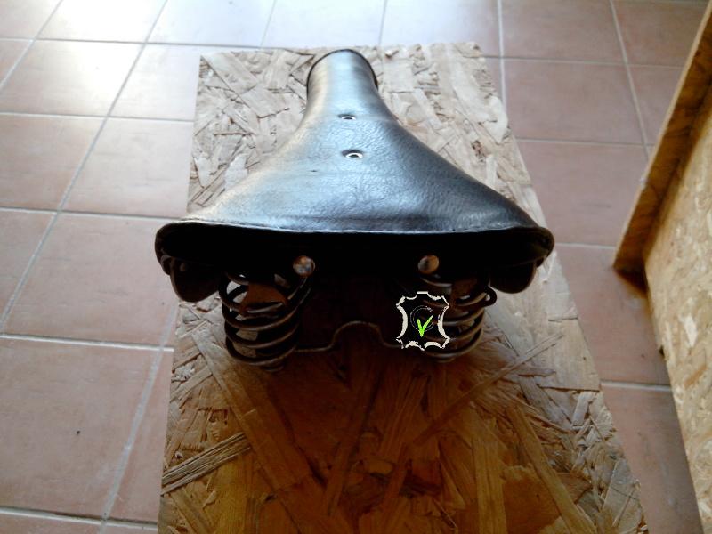 selle de vélo en cuir tendu sur une arature métallique
