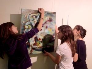 Schülerinnen hängen Bilder für die nächste Vernissage