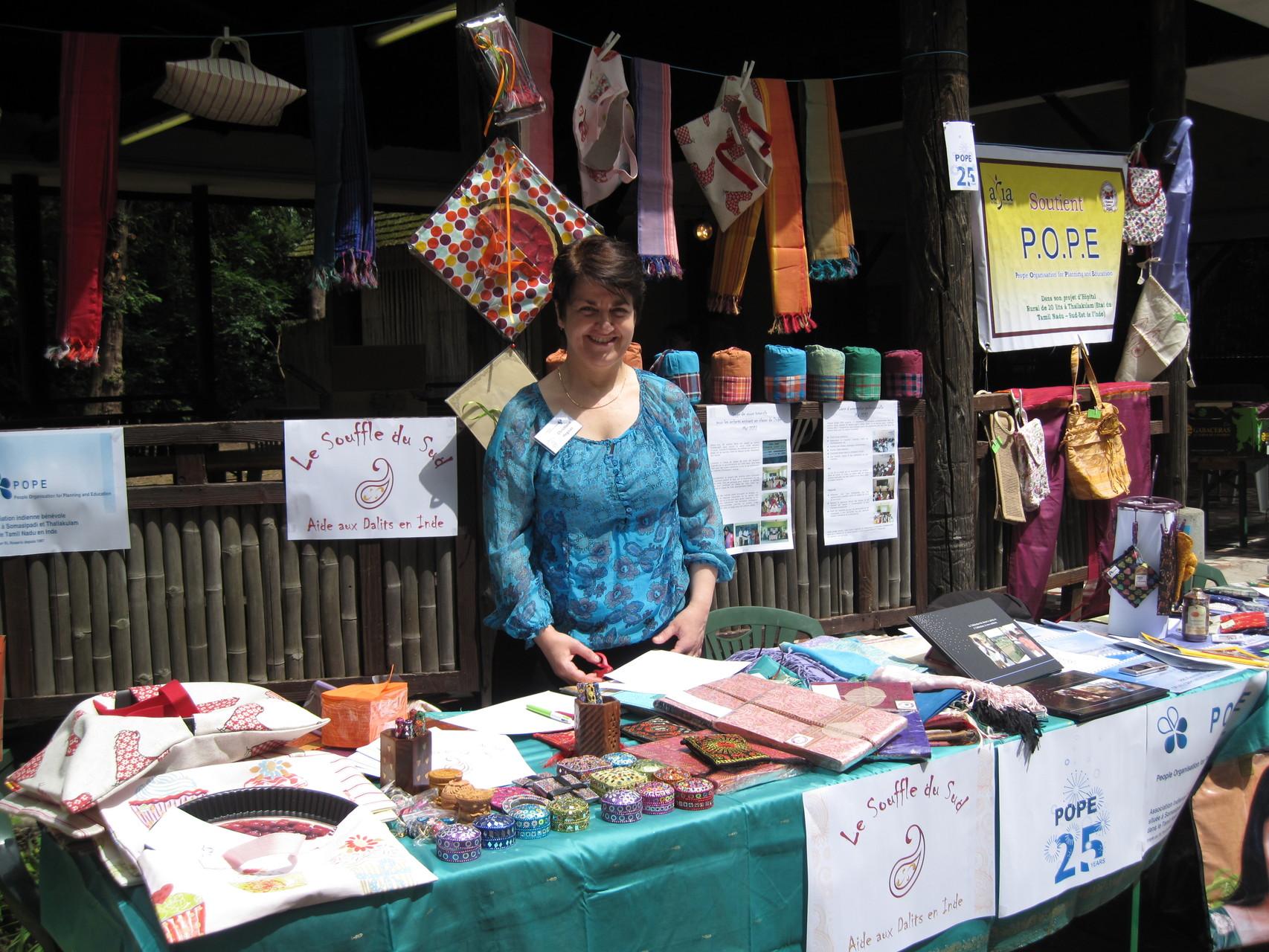 2012 - Christiane derrière le stand bien achalandé en sacs de couchage, sac à tartes, petites boîtes et papeterie indiennes, biscuits apéritifs épicés à l'indienne
