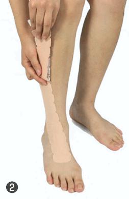 2.テープをやや引きながら足首の中央を通り、外側へ。