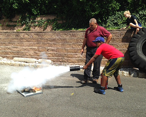 Chief Piccola teaching a student how to put out a fire with a CO2 Extinguisher