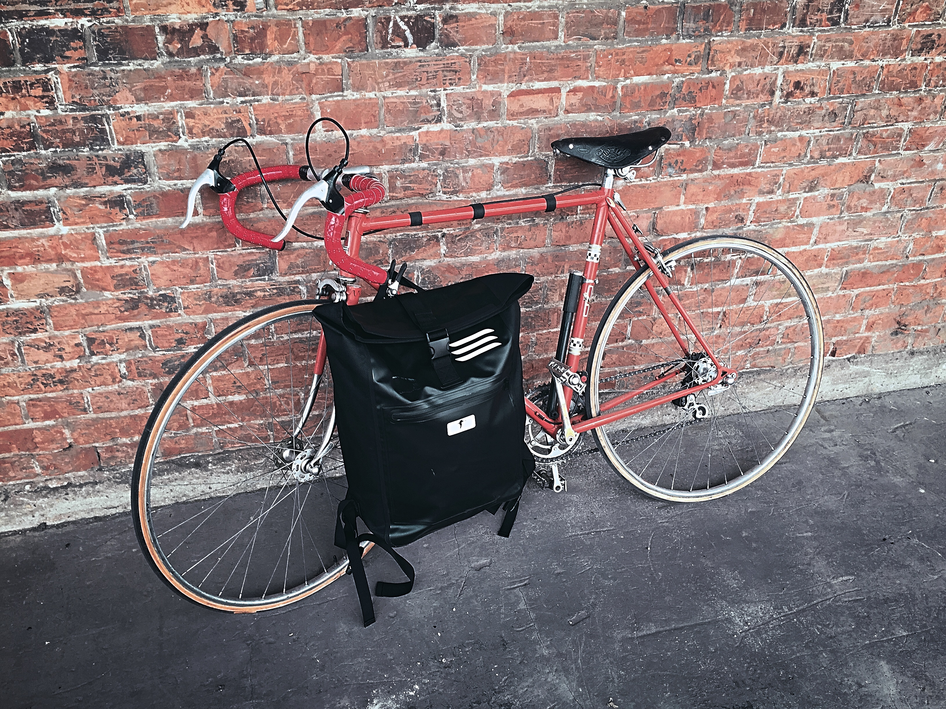 An eine Backsteinmauer ist ein orangefarbenes Rennrad angelehnt. Davor steht ein schwarzer Red Loon Kurierrucksack.