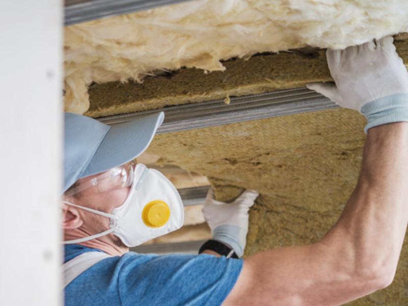 Ein Mitarbeiter der 3B Denkmalpflege & Bausanierung GmbH beim anbringen von Dämmplatten.