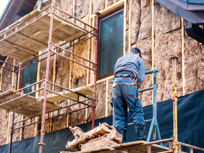 Ein Mitarbeiter der 3B Denkmalpflege & Bausanierung GmbH beim anbringen von WDVS-Dämmplatten an die Außenfassade eines Familienhauses.