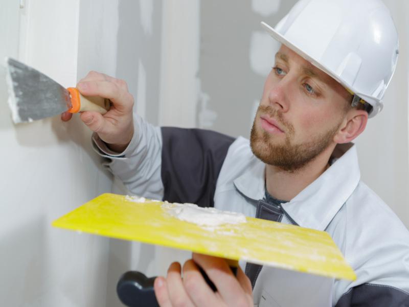 Ein Mitarbeiter der 3B Denkmalpflege & Bausanierung GmbH beim Verspachteln von Trockenbauwänden.