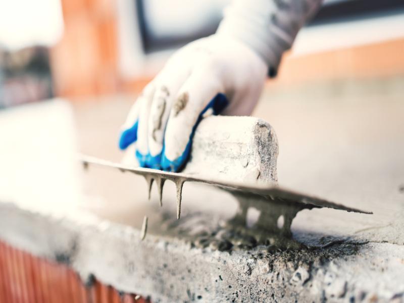Ein Mitarbeiter der 3B Denkmalpflege & Bausanierung GmbH beim Verputzen einer neue Betonschicht.