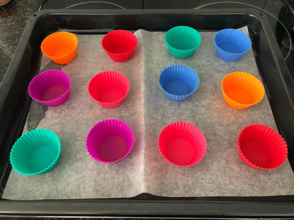 Jetzt den Back-Ofen vorheizen: 180 Grad Ober- und Unter- Hitze. Backpapier und Muffin-Formen auf ein Blech legen.