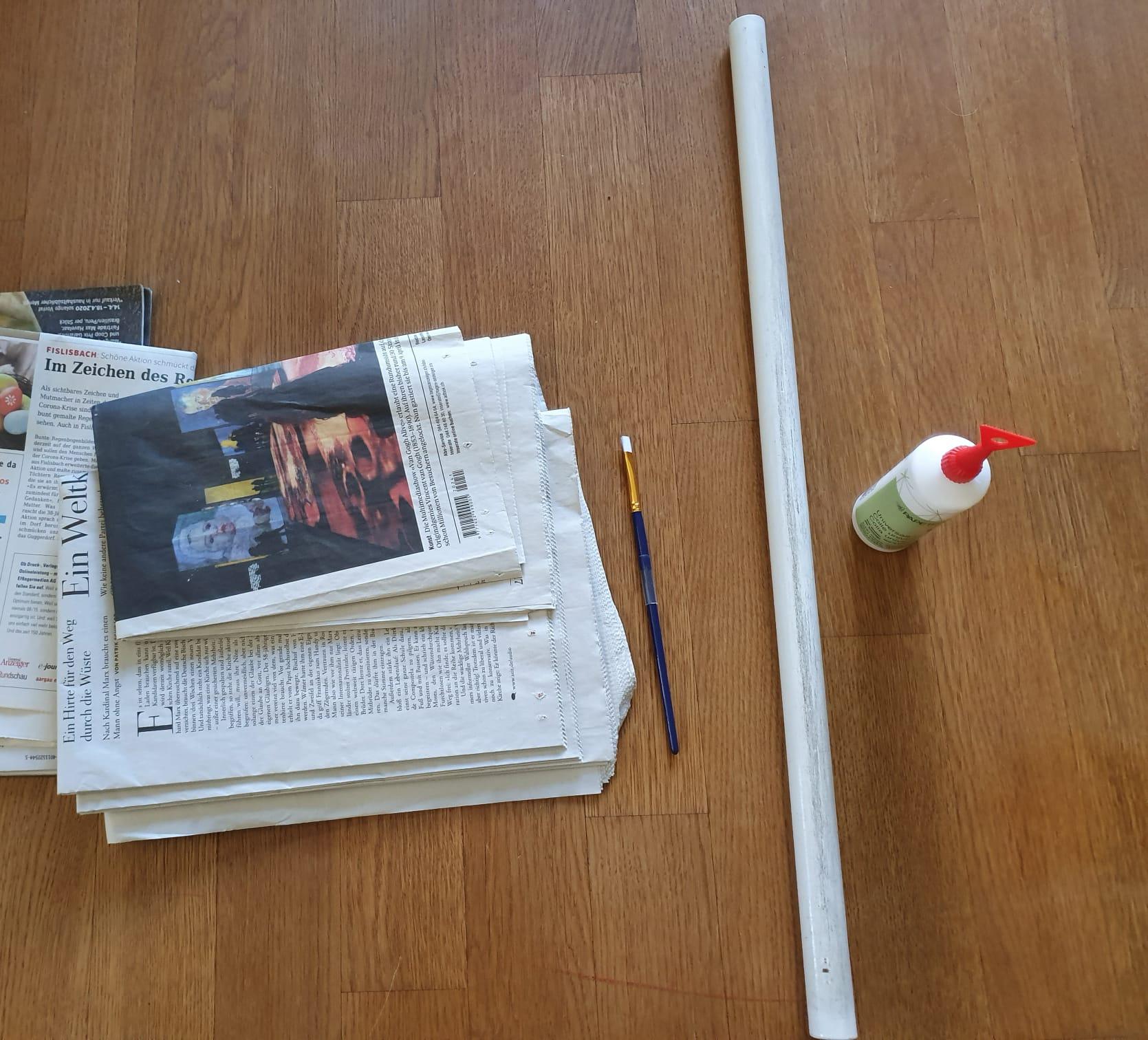 Du brauchst alte Zeitungen (wenn es farbig sein soll, Zeitschriften oder Comics). Leim, einen dünnen Stab oder Stock und einen Pinsel.