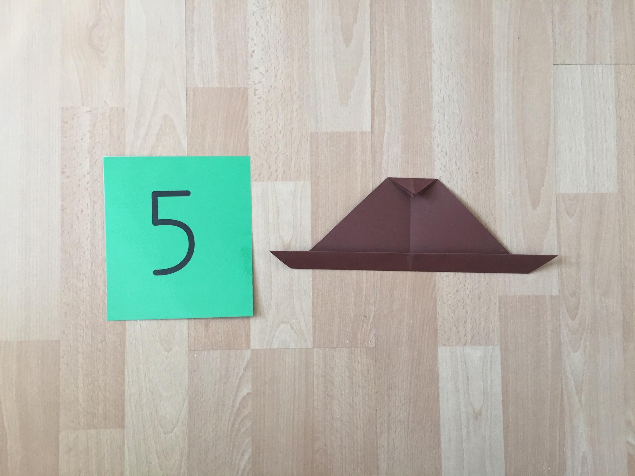 Das kleine Dreieck kannst du wieder zum grossen Dreieck auffalten, den Spitz und den unteren Rand nach innen falten.