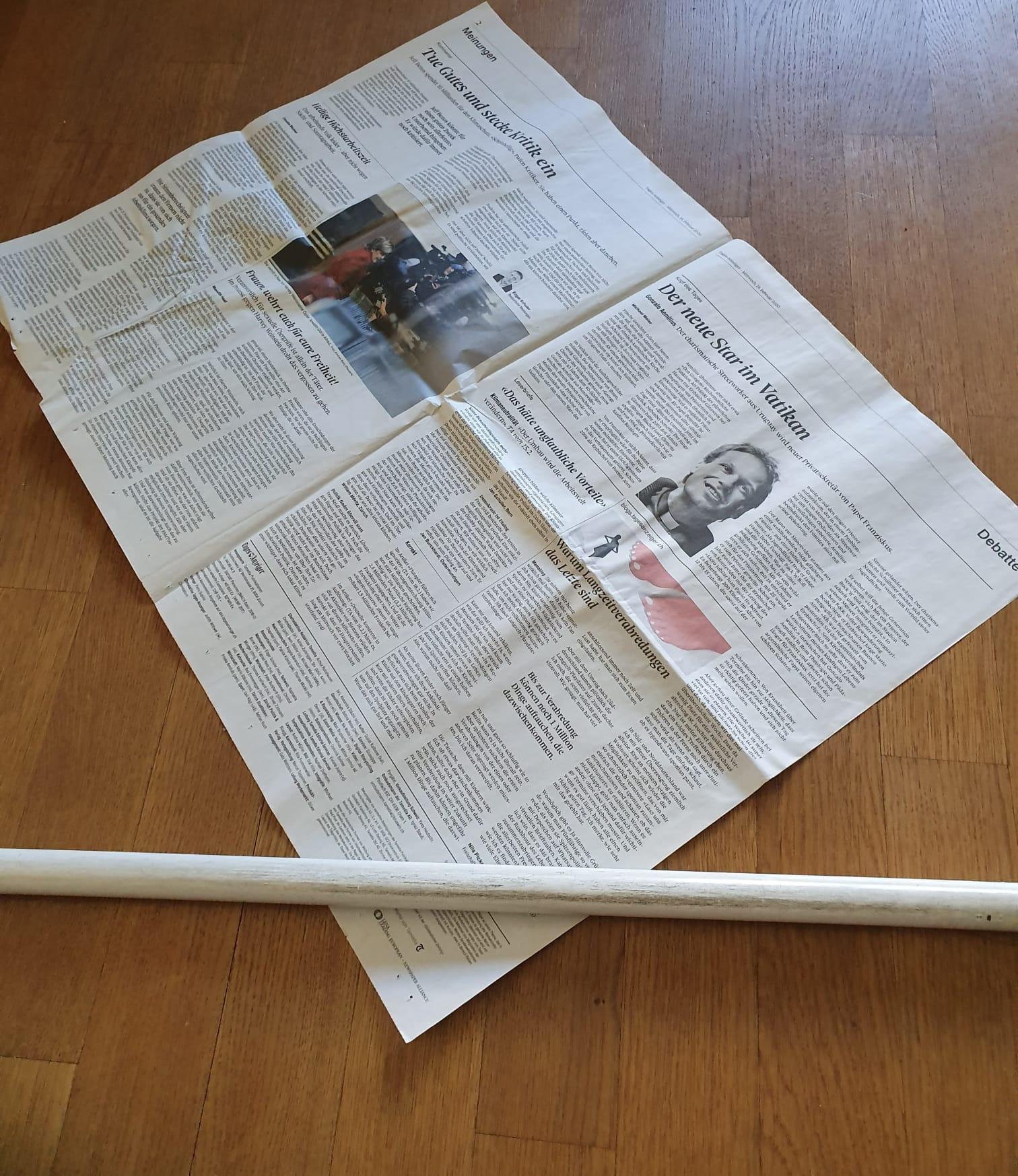 Du nimmst ein Blatt Zeitung. Du legst den Stab in eine Ecke.
