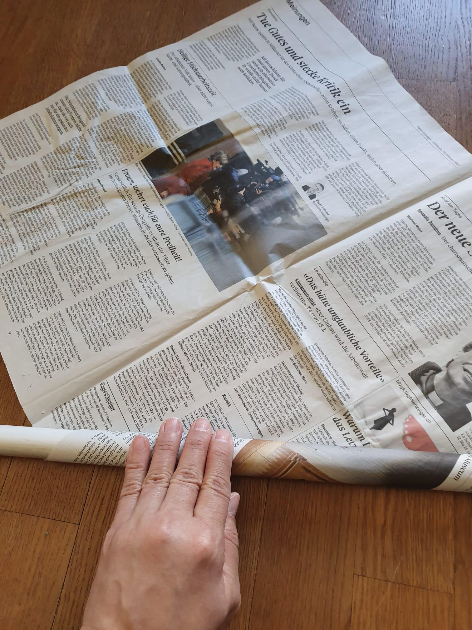 Dann rollst du die Zeitung mit dem Stab auf. Ein wenig drücken, satt aufrollen.