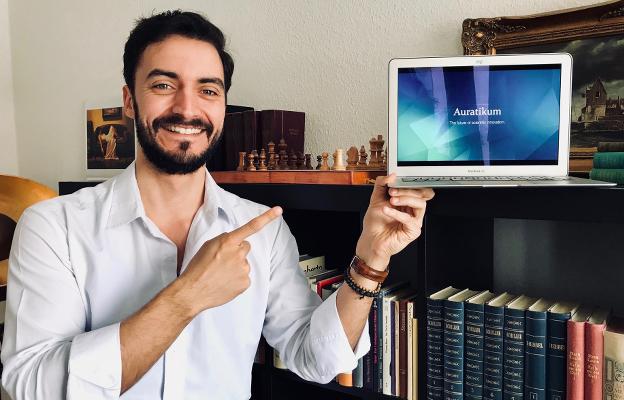 Richard Ottinger mit einem Laptop in der Hand, auf dem, man Auratikum sieht