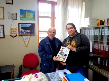Participant of the project presenting calendar to headmaster of high school of Arta