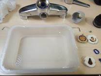 Preparamos un recipiente de plástico con la cantidad de salfuman o desincrustante suficiente para cubrir las piezas del cartucho de la grifería monomando.