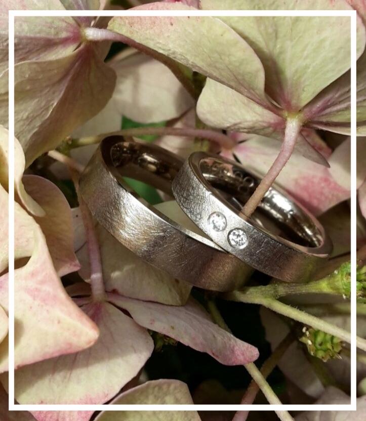 Eheringe in 585/000 Weißgold Damenring mit Brillanten. Der Damenring war zuerst der Verlobungsring mit einem Stein. Den zweiten Brillant gab es zur Hochzeit und vielleicht folgt zum Kind dann ja der Dritte ;-). Eine schöne Art Erinnerungen festzuhalten.