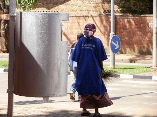 <b>Guillaume RUTEMBESA: Kigali-Straßenkehrerin (wir halten es sauber).</b> Städtische Straßenkehrer/-innen tragen dazu bei, dass Ruanda als das sauberste Land Afrikas gilt. Mülleimer wie vorne im Foto prägen das Stadtbild.