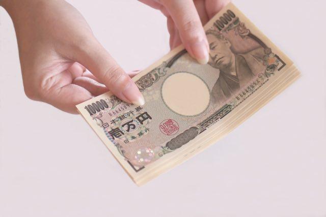 一万円札を渡している人の画像です。