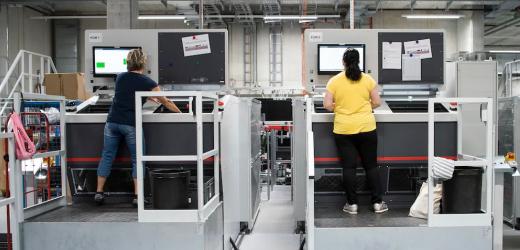 Mitarbeiter arbeiten im vollautomatisierten Logistik-Zentrum von Interdiscount und Microspot in Jegenstorf BE.