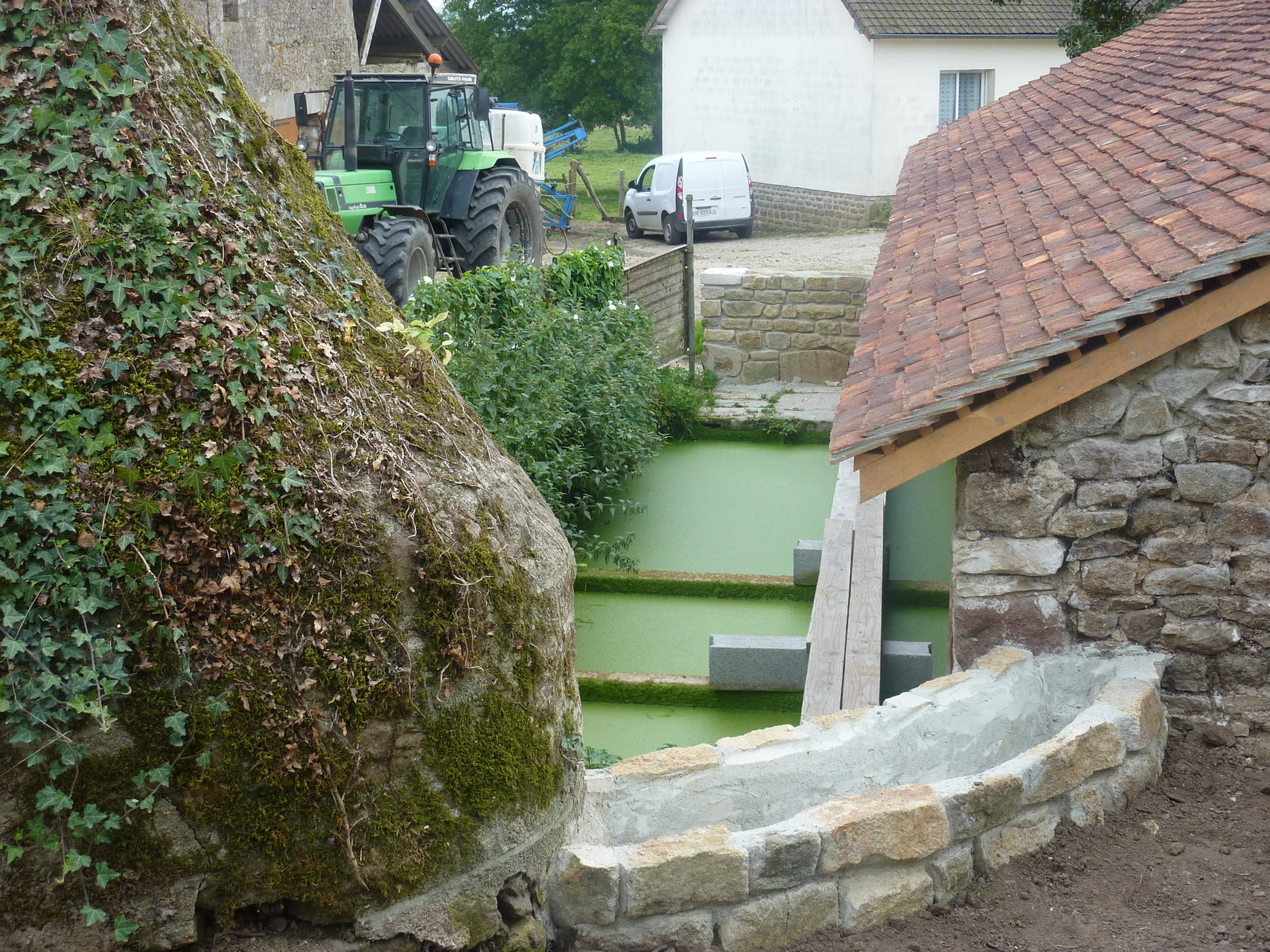 La photo montre le muret entre le puits et le lavoir.