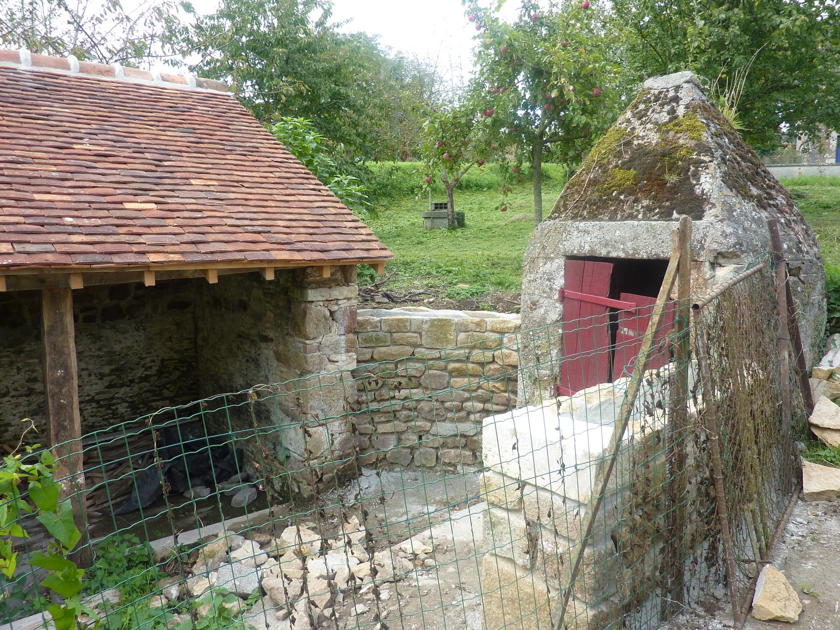 La photo montre les deux murets du côté du puits.