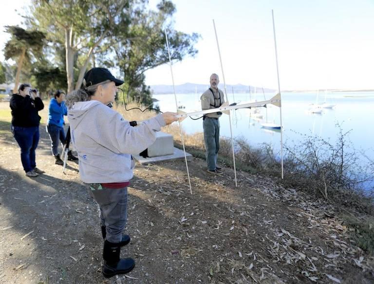 海洋哺乳類センターのボランティア左からウィンターリー・スクリベンとロイス・ペティ、週の魚類野生生物局の生物学者マイケル・ハリスがVHF無線レシーバーを使ってリリース後のラッコを追跡している。