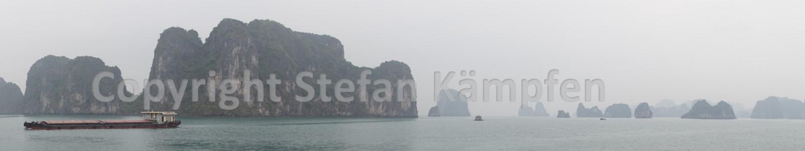 Ein Schiff schippert durch die Irrgärten der Halong Bucht
