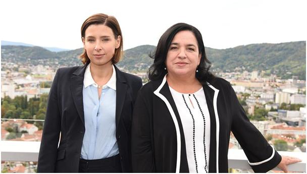 Martina Ebm und Maria Happel, im Hintergrund Berge und eine Stadt im Tal