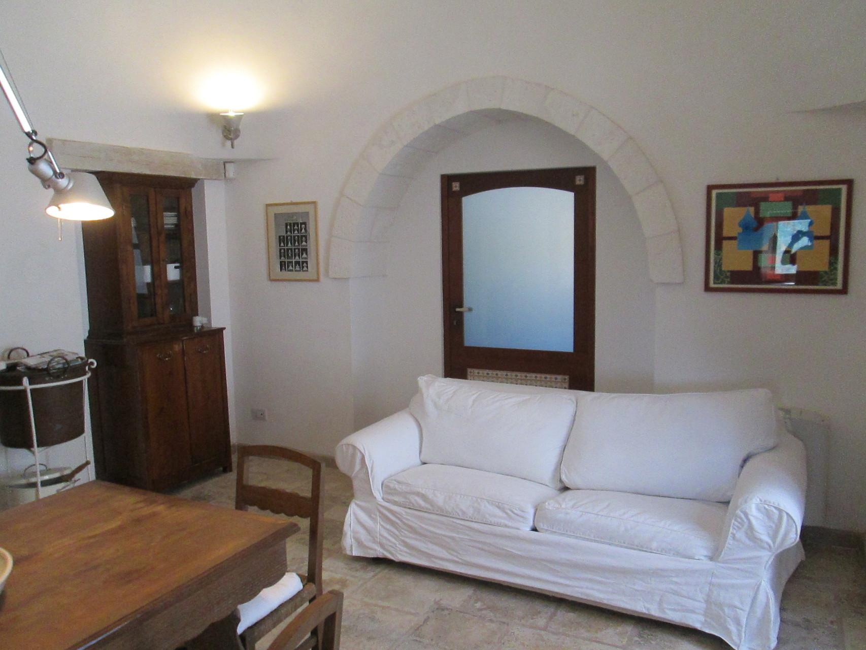 Trullo Ulivo - Soggiorno con divano letto e camino