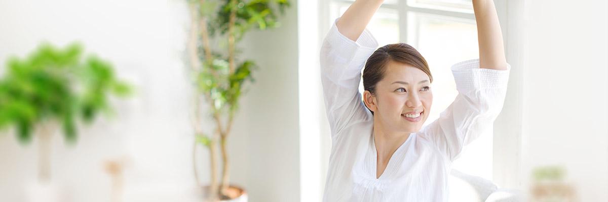 足圧でスッキリ!コリをほぐして身体が楽になった女性。リビングで背伸び。