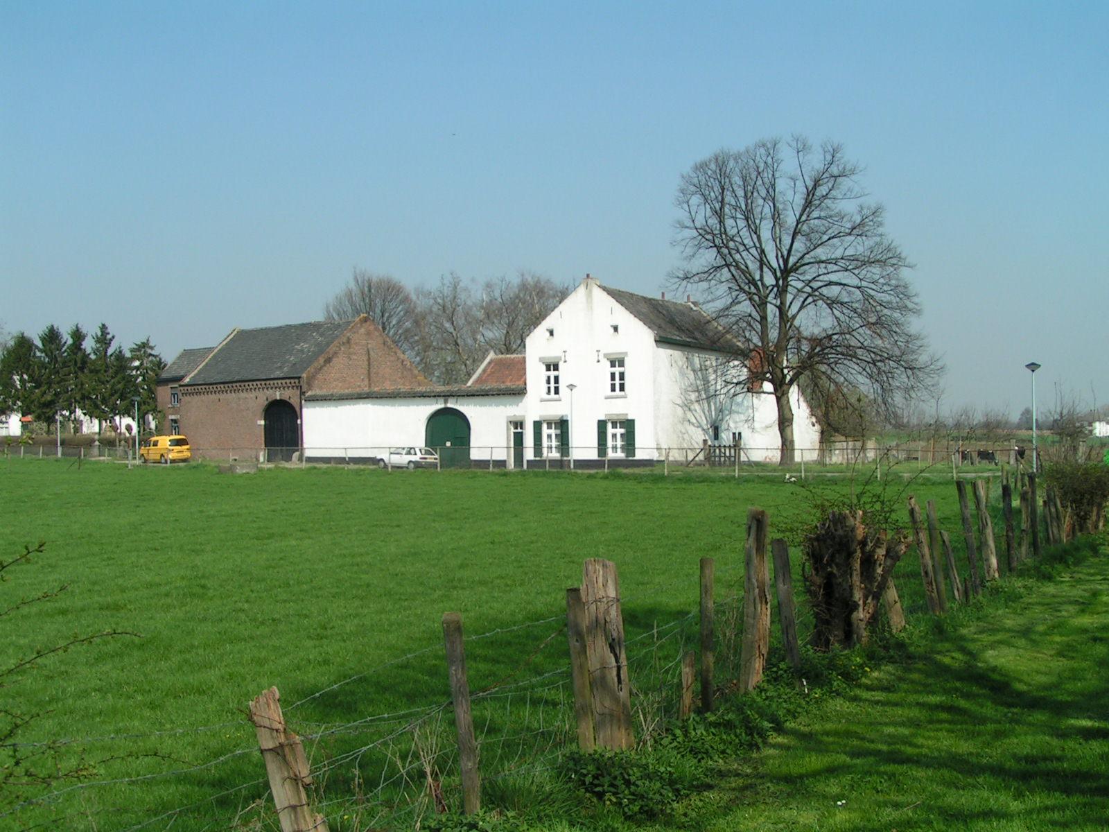 Impressie: boerderijen in een glooiend agrarisch landschap.