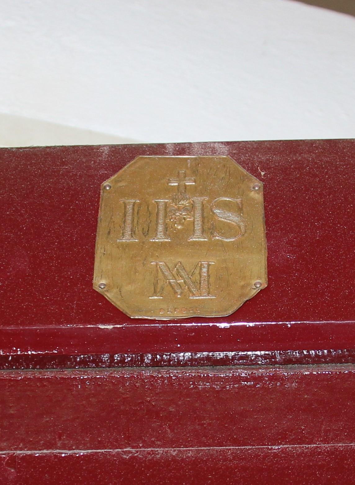 Detail: plaatje met IHS op een souterraindeur, een herinnering aan het retraitehuis