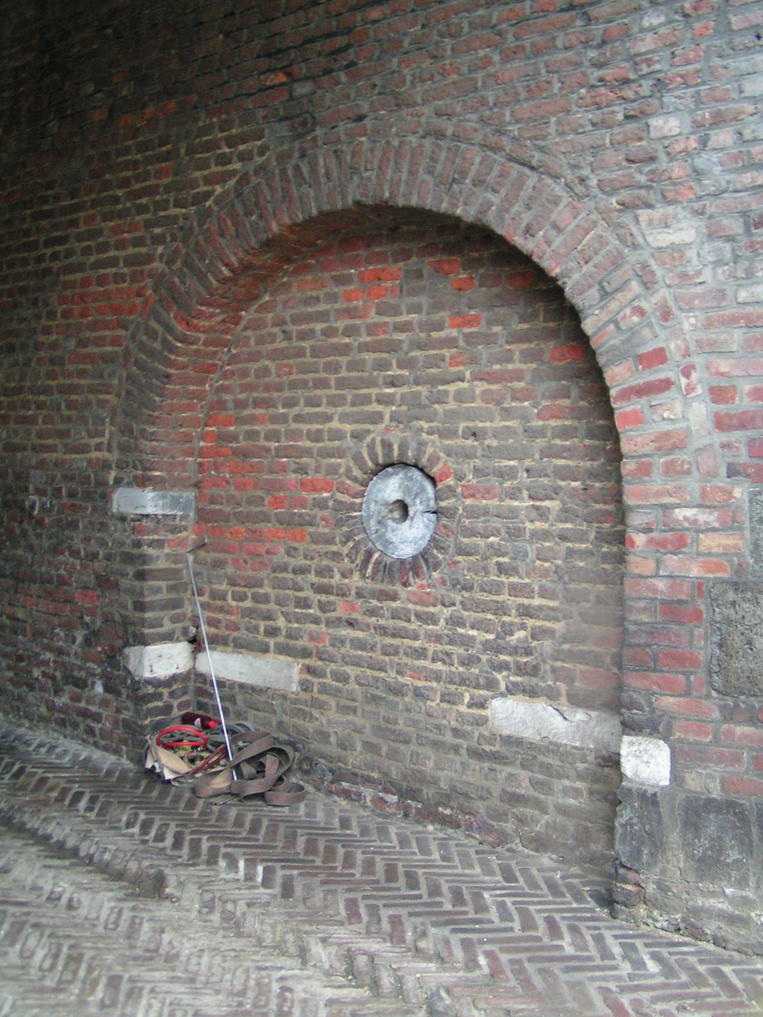 Spaarveld in de onderdoorgang met asgat van het mechaniek van de oorspronkelijke basculebrug.