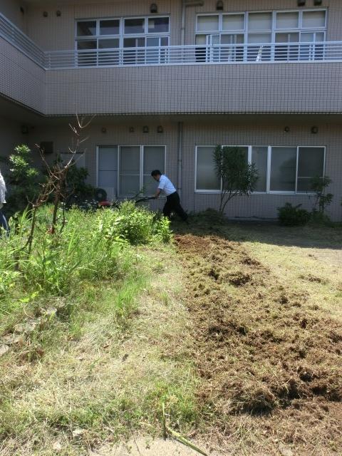 カチコチに固まった花壇を耕うん機で耕すK事務局長。日頃の運動不足も解消?