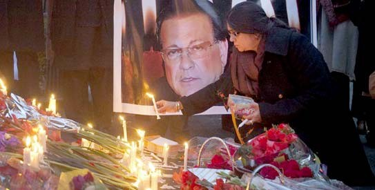 A woman lights a candle next to an image of the governor of Punjab Salman Taseer during a candlelight vigil in commemoration of Taseer. - Photo by Reuters (File Photo)