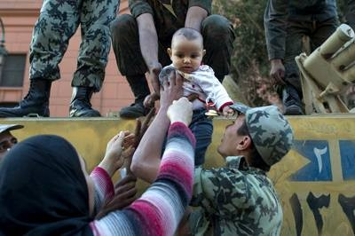An Egyptian woman takes her son back after taking a picture of him with soldiers at Cairo's Tahrir Square on Sunday (AFP photo by Pedro Ugarte)