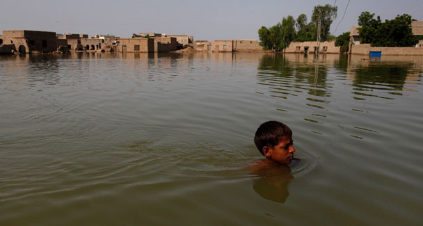 A flood victim wades through floodwaters while he leaves his village of Bello Patan for higher ground in Dadu, some 320 kilometres (198 miles) north of Karachi, September 13, 2010. – Reuters