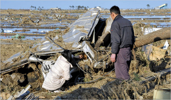 Parents look at the body of their daughter they found in the vehicle of a driving school in Yamamoto, Miyagi Prefecture