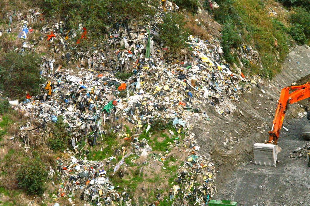 Ammasso di rifiuti della vecchia deponia ancora scoperti che poi in caso di forte vento volano in parte nel bosco circostante verso la frazione di Sorte