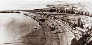 """Les Fusiliers Mont Royal vont débarquer au centre de la plage parmi les LCT et les tanks. On aperçoit à droite le casino. Au fond à droite la falaise d'où tirait la batterie """"Bismark"""""""