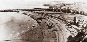The Fusiliers Mont Royal land in the center of the beach, among the LCT and the tanks. To the right of the photo is the casino. To the extreme bottom right of the photo is the cliff top from where the Bismarck Battery was firing.