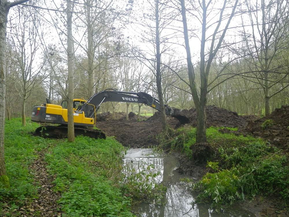 Comblement grossier du bief à l'aide de la pelle avant le passage d'un bulldozer pour niveler uniformément la zone des travaux