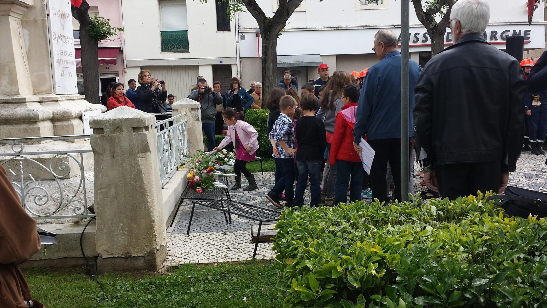 ENFANTS DÉPOSANT COMME UNE DIZAINE D'AUTRES, UNE MULTITUDE DE FLEURS, LE 8 MAI 2014 À STE-LIVRADE
