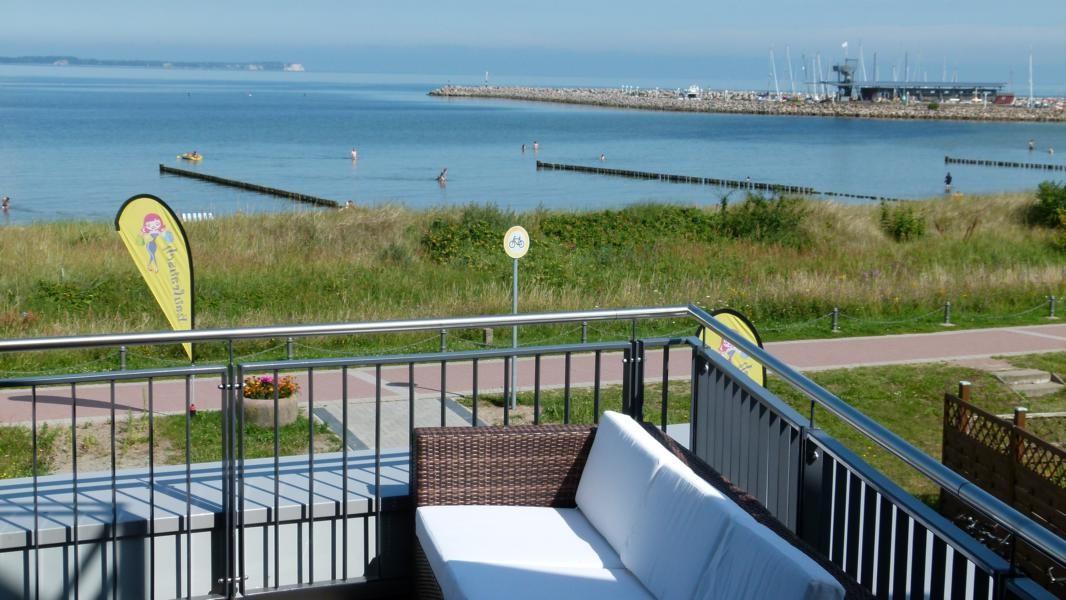 Loungemöbel auf der Dachterrasse mit Blick auf die Badegäste in der Ostsee